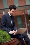 Happy businessman sitting outdoors with laptop Stock Photos