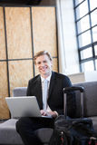 Happy businessman sitting on sofa and using laptop Royalty Free Stock Photography