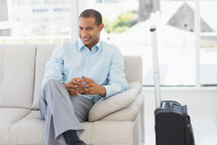 Happy businessman sitting on sofa waiting to depart on business trip Stock Image