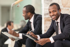 Happy businessman sitting on stairs Stock Photography