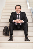 Happy businessman sitting on stairs Stock Photo