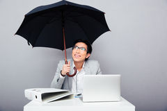 Happy businessman sitting at the table with umbrella Stock Photography