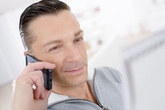 Happy businessman sitting and talking on phone at office Stock Photos
