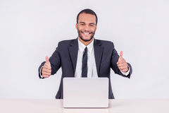 Happy businessman. Smiling African businessman sitting at a desk Royalty Free Stock Photography