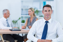 Happy businessman smiling at camera with colleagues behind Royalty Free Stock Photos