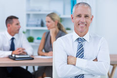 Happy businessman smiling at camera with colleagues behind Royalty Free Stock Images