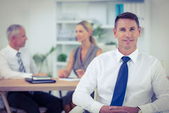 Happy businessman smiling at camera with colleagues behind Stock Photo