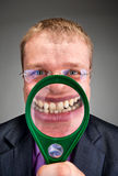 Happy businessman smiling through magnifier Royalty Free Stock Photo