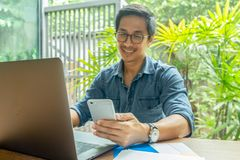Happy businessman smiling while reading his smartphone with laptop on table. royalty free stock photos