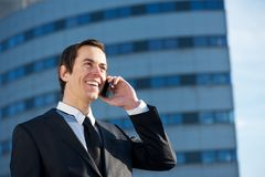Happy businessman smiling and talking on mobile phone outdoors Stock Photos