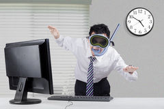 Happy businessman with snorkeling equipment. Young businessman wearing snorkeling equipment and posing to swim in the office with computer on desk Stock Photo