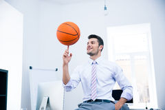 Happy businessman spining ball in office Stock Image