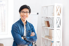 Happy businessman standing with arms crossed in office Stock Images