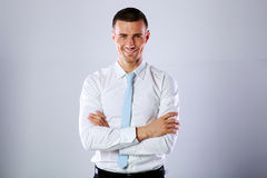 Happy businessman standing with arms folded Stock Photo