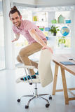Happy businessman standing on chair in office Royalty Free Stock Photos