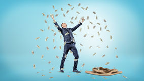 A happy businessman standing beside an empty sack with hands raised up while catching falling dollar bills. Royalty Free Stock Photos