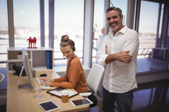 Happy businessman standing while female colleague working in office Stock Image