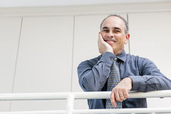 Happy businessman standing in hallway. Portrait of smiling proud business man standing in office hallway leaning on railing with copy space stock photography