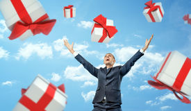 A happy businessman standing with hands raised in victory motion under a rain of gift boxes falling on him. Stock Photo