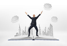 Happy businessman standing with his arms up on big opened book Royalty Free Stock Images
