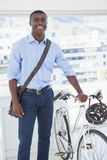 Happy businessman standing with his bike Royalty Free Stock Photos