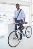 Happy businessman standing with his bike Stock Photo