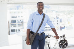 Happy businessman standing with his bike Stock Image