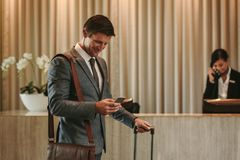 Business traveler arriving at his hotel. Happy businessman standing in hotel lobby and using mobile phone. Business traveler arriving at his hotel with phone and Stock Images