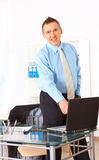 Happy businessman standing in office Royalty Free Stock Photos
