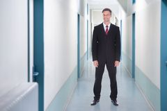 Happy Businessman Standing In Office Corridor Stock Photo