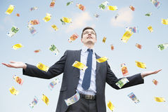 Happy businessman standing in the rain of money. Happy businessman standing in the rain of euro money. Euro are falling from the sky royalty free stock photo
