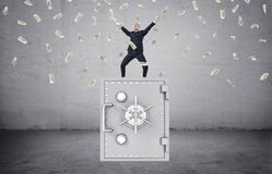 Happy businessman standing on safe and lot of money in the air Stock Image