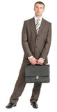 Happy businessman standing with suitcase Royalty Free Stock Photography