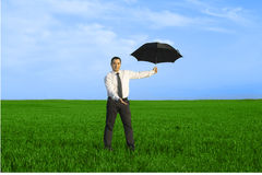 Happy businessman standing with umbrella. In the meadow Royalty Free Stock Photos