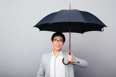 Happy businessman standing with umbrella Royalty Free Stock Photography