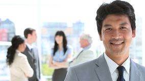 Happy businessman standing upright in front of his team Stock Photography