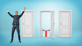 A happy businessman stands close to three doors where only one is open with a gift box inside. Stock Image