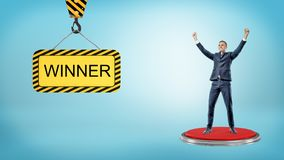 A happy businessman stands on a red pushbutton near a construction sign reading Winner. Royalty Free Stock Photo