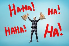 A happy businessman in a striped jail suit and a mask holds money bags above his head near large words Ha-Ha. Happy and rich. Stolen money. Loads of cash royalty free stock images