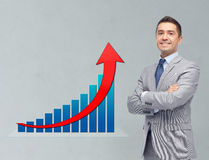 Happy businessman in suit with growth chart Stock Images