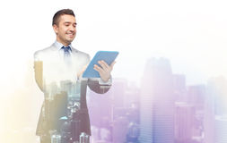 Happy businessman in suit holding tablet pc Royalty Free Stock Photography