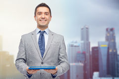 Happy businessman in suit holding tablet pc stock photos