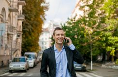 Happy businessman in suit with laptop in the city stock photography