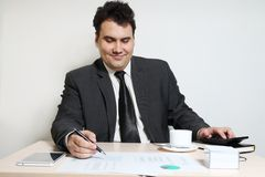 Happy businessman in suit looks at documents at table. With coffee, diagrams, documents, tablet PC stock photo