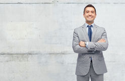 Happy businessman in suit over concrete wall Stock Photos
