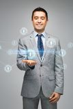 Happy businessman in suit showing network contacts. Business, people, technology, connection and communication concept - happy businessman in suit showing royalty free stock photography