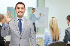Happy businessman in suit showing ok hand sign Stock Photography