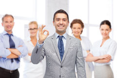 Happy businessman in suit showing ok hand sign Royalty Free Stock Photography