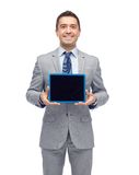 Happy businessman in suit showing tablet pc screen Royalty Free Stock Photography