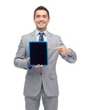 Happy businessman in suit showing tablet pc screen Stock Images